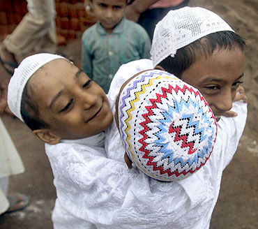 Muslim boys greet one another after offering Eid al-Fitr prayers outside a mosque at Noida