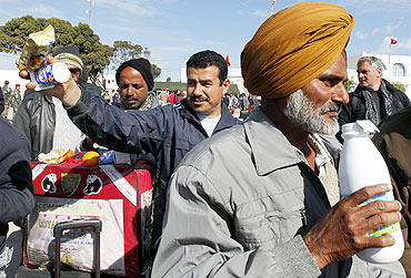 Indian migrants fleeing unrest in Libya receive refreshments at the Tunisian border crossing of Ras Jdir