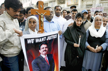 Christians hold a cross and a poster of slain Minister for Minorities Shahbaz Bhatti, during a protest in Hyderabad to condemn his assassination
