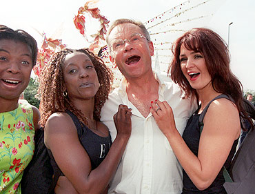 Jeffrey Archer, centre, sings along with revellers at the annual Notting Hill Carnival in London