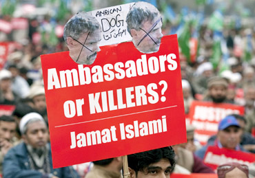 A supporter of Jamaat-e-Islami holds a placard during a protest rally against Davis