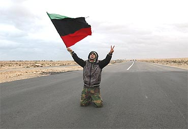 An anti-Gaddafi rebel prays and chants along a road