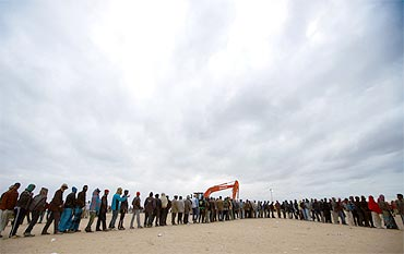 Evacuees line up for food distribution at an UNHCR refugee camp near the border crossing of Ras Jdir after fleeing violence in Libya