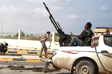 An anti-Gaddafi rebel fires an anti-aircraft gun