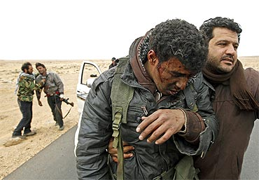 Injured rebels are helped out of a car during a battle along the road between Ras Lanuf and Bin Jiwad
