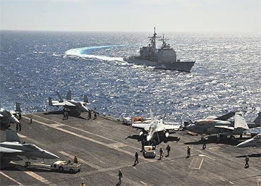 The missile cruiser USS Leyte Gulf pulls alongside the aircraft carrier USS Enterprise while conducting flight operations in the Red Sea