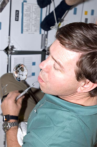 NASA astronaut Michael Barratt watches a water bubble float freely near him on the middeck of space shuttle Discovery