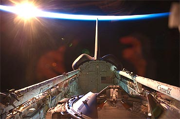 An orbital sunrise brightens this view of space shuttle Discovery's vertical stabilizer
