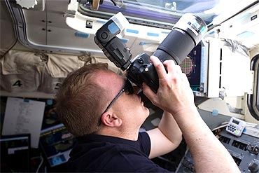 NASA astronaut Eric Boe, STS-133 pilot, uses a still camera at an overhead window on the aft flight deck of Discovery to photograph the ISS