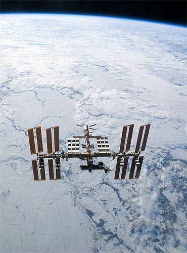 The ISS is seen in this view from the Discovery with the earth's horizon in the background