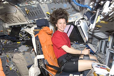 NASA astronaut Catherine Coleman, Expedition 26 flight engineer, occupies the commander's station on the flight deck of Discovery