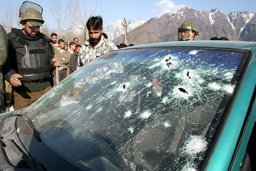 Security personnel look at the gunned down vehicle of slain JeM commander Sajad Afghani near Dal Lake on Thursday