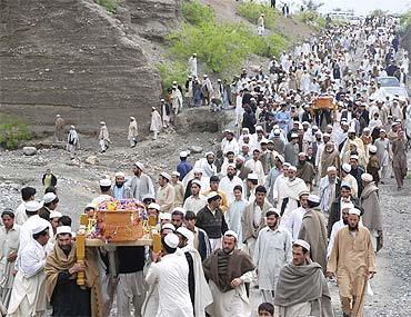 Pakistani tribesmen carry coffins during the funeral procession of victims of a suicide blast