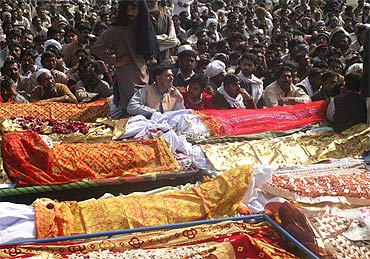 Residents gather near the bodies of bomb blast victims during a funeral ceremony in Dera Ismail Khan