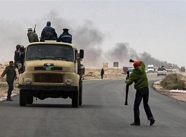 Anti-Gaddafi rebels retreat after coming under rocket fire during clashes with pro-Gaddafi forces near Ras Lanuf