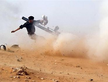 A rebel fighter fires a cannon during a battle near Ras Lanuf