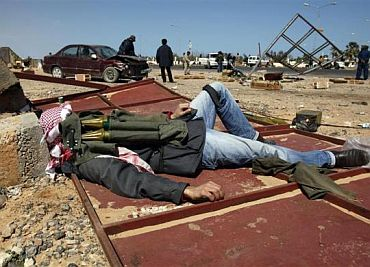 A rebel fighter lies down with ammunition on him near the oil facility of Ras Lanuf