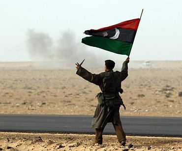 A rebel fighter holds a Kingdom of Libya flag and a knife during shelling by soldiers loyal to Libyan leader Muammar Gaddafi in a battle near Ras Lanuf