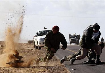 Rebel fighters jump away from shrapnel during heavy shelling by forces loyal to Libyan leader Muammar Gaddafi near Bin Jawad