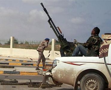 An anti-Gaddafi rebel fires an anti-aircraft gun during clashes with pro-Qaddafi forces in Ras Lanuf