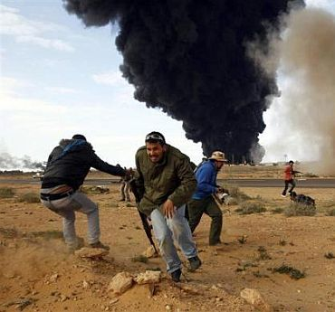 Rebel fighters run for cover in front of a burning gas storage terminal during a battle on the road between Ras Lanuf and Bin Jawad