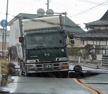 A truck is stuck on a road crack after a powerful earthquake in Iwaki, Fukushima Prefecture