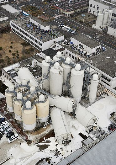 Evacuated employees are pictured near toppled tanks a brewery in Sendai, Miyagi Prefecture