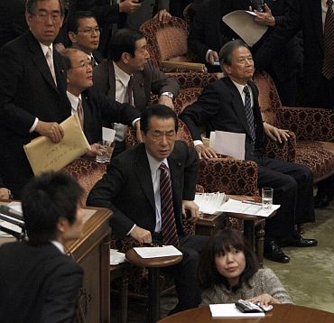 Japan's Prime Minister Naoto Kan (C) reacts he feels the quake in the upper house of parliament