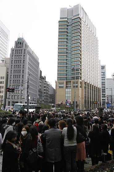 People stand outdoors after evacuating from nearby buildings in Tokyo's financial district