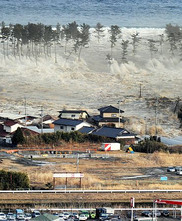 A massive tsunami sweeps in to engulf a residential area after a powerful earthquake in Natori, Miyagi Prefecture in northeastern Japan