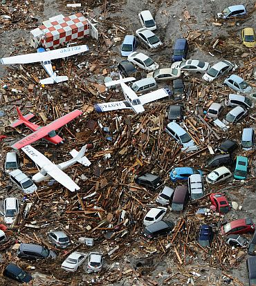 Cars and airplanes swept by a tsunami are pictured among debris at Sendai Airport