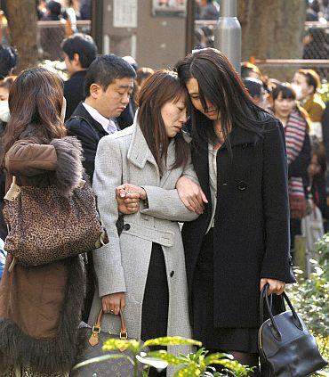 Evacuees stand around Shinjuku Central Park in Tokyo