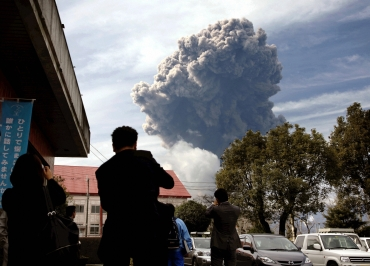 Smoke rises from Shinmoedake peak, a mountain in the Kirishima volcanic range between Kagoshima and Miyazaki prefectures, as people watch from Takaharu town, southern Japan