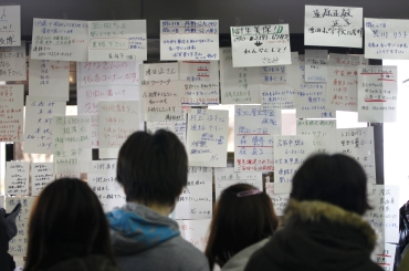 Residents search for the names of their missing family members and relatives at a temporary information centre organised by the local government after their villages were hit by the earthquake and tsunami in Sendai, northeastern Japan