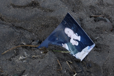 A family photograph is half buried in the mud in Rikuzentakata after it was a destroyed by an 8.9 magnitude earthquake and tsunami