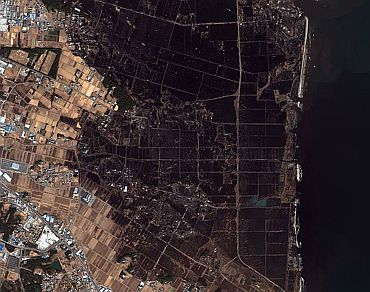This is a handout satellite image showing damage after an earthquake and tsunami in Minamisoma
