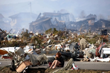 A woman cries while sitting on a road amid the destroyed city of Natori, Miyagi Prefecture