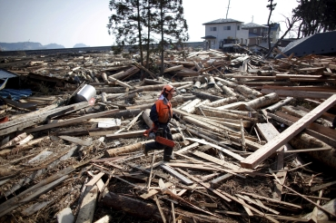 An emergency worker walks amidst debris in an area hit by an earthquake and tsunami in Kuji, Iwate