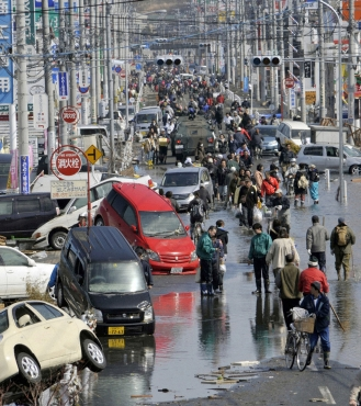 People walk along a flooded street in Ishimaki City, Miyagi Prefecture