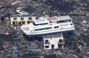 A ferry is perched on top of a house in the aftermath of an earthquake and tsunami in Otsuchi, Iwate