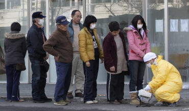 People queue to be screened by a technician in protective gear for signs of possible radiation in Nihonmatsu, northern Japan
