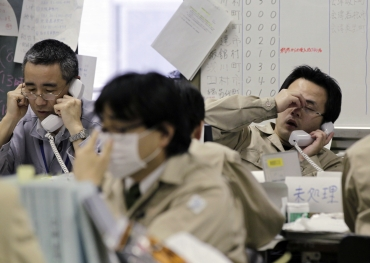 Workers at the disaster response headquarters speak on telephones in Fukushima, northern Japan