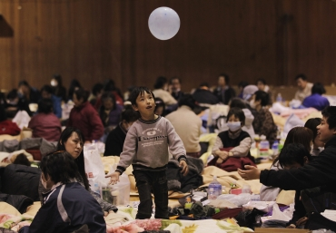 A boy plays with a balloon at an evacuation centre set in a gymnasium in Kawamata, Fukushima Prefecture in northern Japan
