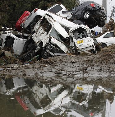 Destroyed cars are seen at a factory area devastated by earthquake and tsunami in Sendai