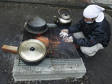 An evacuee prepares dinner in a makeshift shelter converted from a temple at Minamisanriku town, Miyagi Prefecture in northern Japan