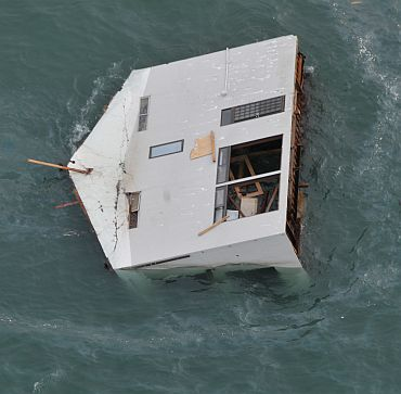 Seen from an HH-60G helicopter, a house drifts in the ocean east of Sendai, in this US Air Force handout photo dated March 14