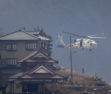 A rescue helicopter lowers a man in search of victims along a remote hillside near Kesennuma City on March 15