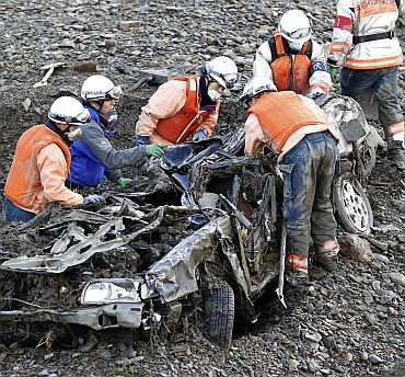 Rescue workers search for a body after digging a car out of the debris in Minamisanriku town