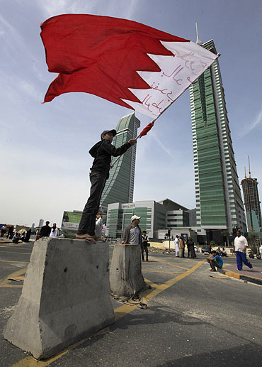 An anti-government protester waves the Bahraini flag as he stands on a roadblock used to prevent riot police from entering the junction of Bahrain Financial Harbour in Manama