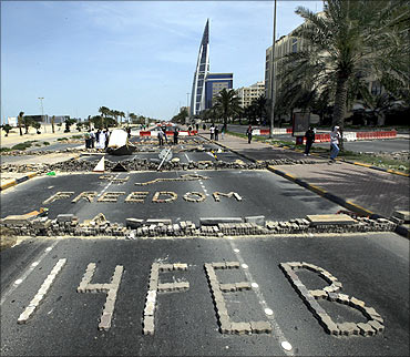 Anti-government protesters form the words Freedom and 14 Feb with bricks as they block the roads from riot police at the junction of Bahrain Financial Harbour in Manama